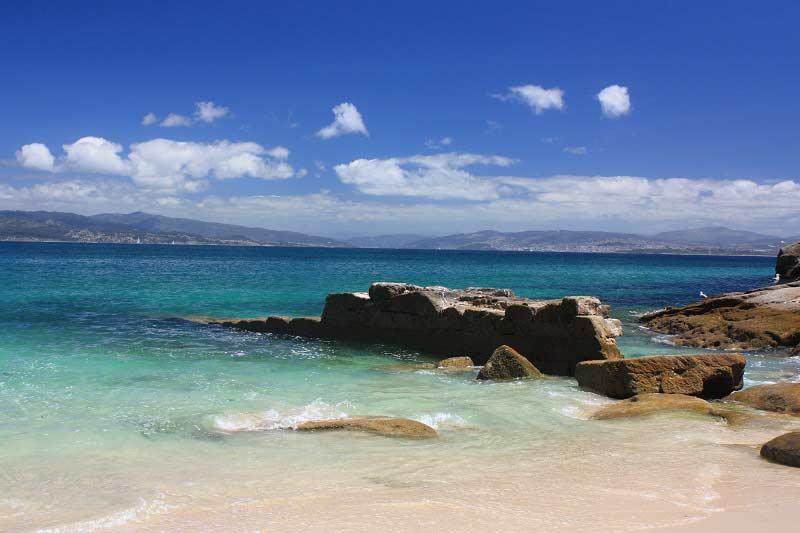 El embarcadero de San Martiño rodeado por una playa paradisíaca de aguas cristalinas